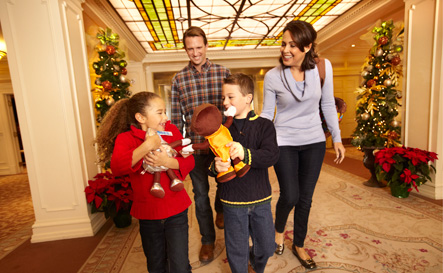 Family of 4 walking through the holiday decorated lobby at The Hotel Hershey