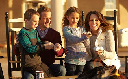 Family toasting marshmellows in a firepit on the Veranda of the hotel hershey