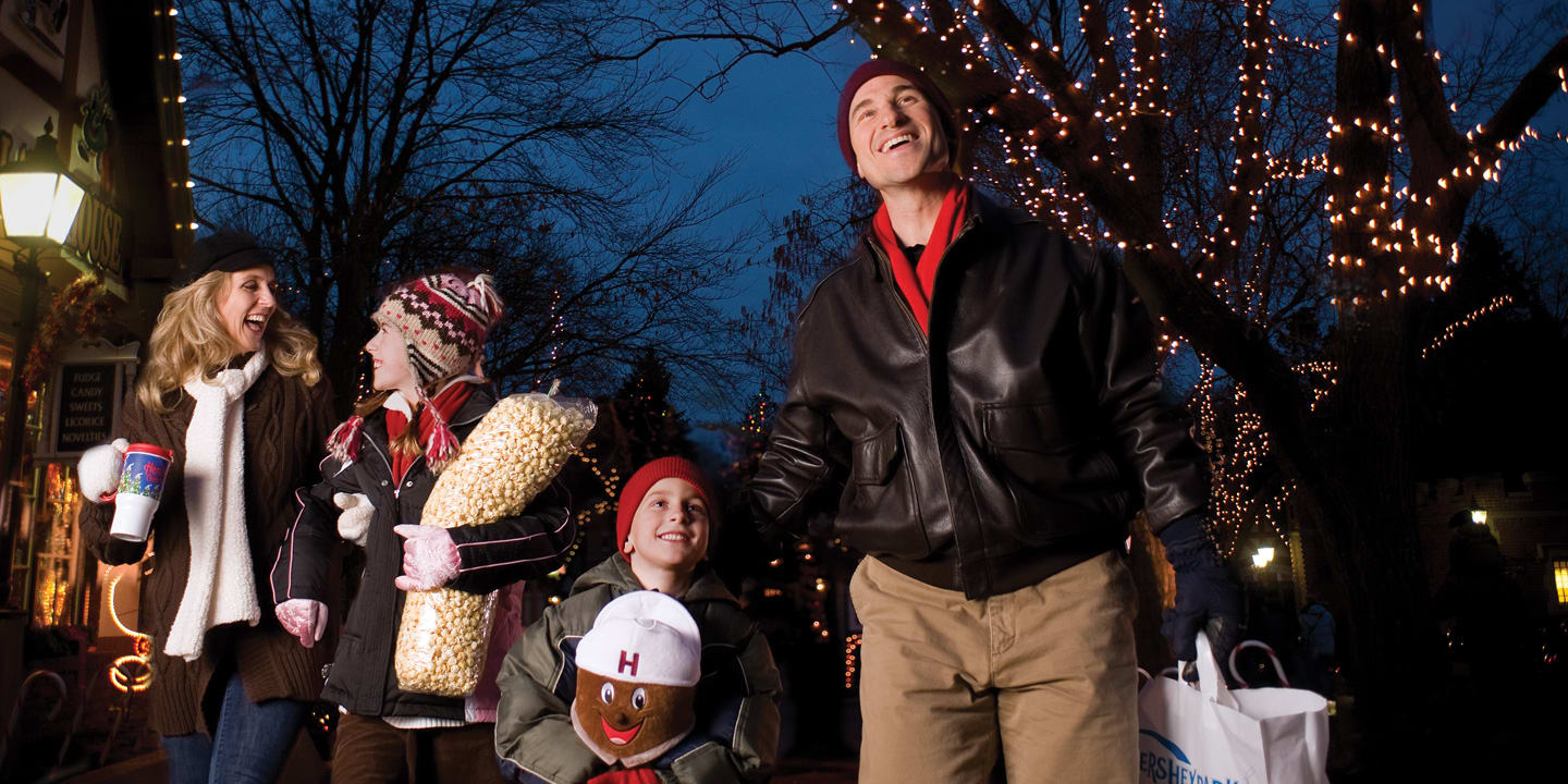 family in winter coats walking through hersheypark christmas candylane