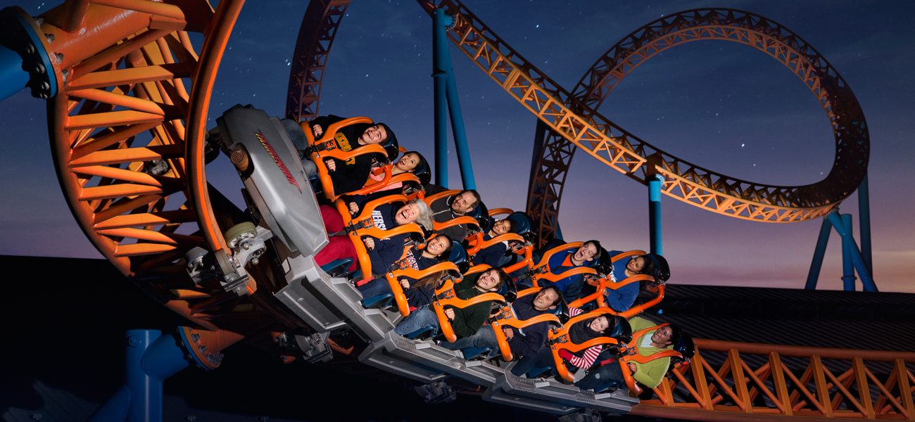 people riding Fahrenheit roller coaster in the dark with a starry night sky in the background