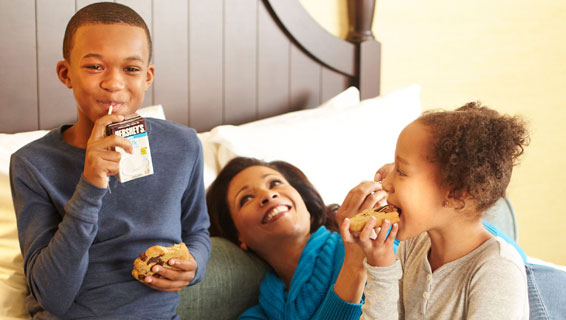 Mother and Children enjoying cookies in bed